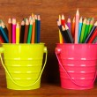 Colorful pencils in two pails on wooden background — Stok fotoğraf