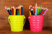 Colorful pencils in two pails on wooden background — Stock Photo
