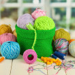 Colorful yarn for knitting in green basket on wooden table on window background — Stock Photo #23930245
