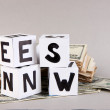 White paper cubes labeled &quot;News&quot; with money on grey background - Stock Photo