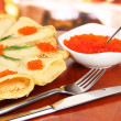 Delicious pancakes with red caviar on table in cafe - Stock Photo