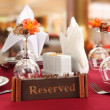 Reserved sign on restaurant table with empty dishes and glasses — Stock Photo #23939951