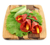 Salami rolls with paprika pieces inside, on wooden board, isolated on white — Stock Photo