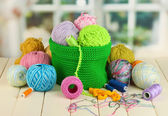Colorful yarn for knitting in green basket on wooden table on window background — Stock Photo