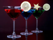 Alcoholic cocktails in martini glasses on dark red background — Stock Photo