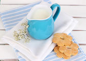 Blue jug with milk and cookies on wooden picnic table close-up — Stock Photo