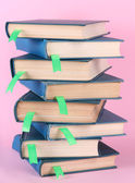Many books with bookmarks on pink background — Stock Photo
