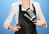 Hairdresser in uniform with working tools, on color background — Stock Photo