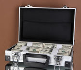 Suitcase with 100 dollar bills on brown background — Stock Photo