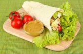Kebab - grilled meat and vegetables, on wooden board, on bamboo mat background — Stock Photo