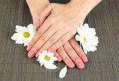 ピンクのマニキュアと竹マットの背景に花を持つ女性手 — ストック写真