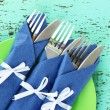 Forks and knives wrapped in blue paper napkins, on color wooden background - Stock Photo