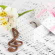 Treble clef, flower and box holding wedding ring on musical background - Stock Photo