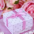 Rose and gift box on pink cloth — Stock Photo