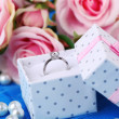 Rose and engagement ring on blue cloth — Stock Photo