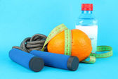 Orange with measuring tape,skipping rope and bottle of water, on color background — Stock Photo