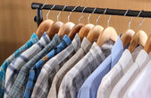 Men's shirts on hangers in wardrobe — Stok fotoğraf