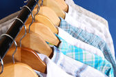 Men's shirts on hangers on blue background — Stockfoto
