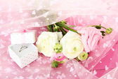 Ranunculus (persian buttercups) and engagement ring, on pink cloth — Foto de Stock