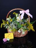 Boeket van bloemen in mand geïsoleerd op zwart — Stockfoto