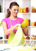 Beautiful young woman wipes clean utensils in kitchen — Stock Photo
