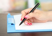 Female hand writing, on bright background — Stock Photo