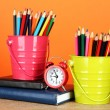 Photo: Colorful pencils in two pails with writing-pad on table on orange background