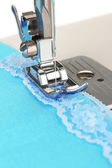 Closeup of sewing machine working part with blue cloth — Stock Photo