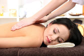 Hermosa joven en el salón de spa recibiendo masaje, sobre fondo brillante — Foto de Stock