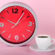 Cup coffee and clock on pink background — Стоковая фотография