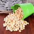 Overturned bucket with grains on wooden background - Stock Photo