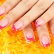 Closeup of hands of young woman with elegance manicure on bright background - Stock Photo