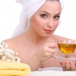 Beautiful young woman with towel on her head and cup of herbal tea isolated on white — Stock Photo