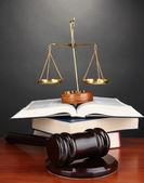 Dřevěné kladívko, zlaté váhy spravedlnosti a knih o šedé pozadí — Stock fotografie