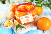 Orange jam with zest and tangerines, on blue wooden table — Stock Photo