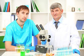 Physician and assayer during research on room background — Foto de Stock