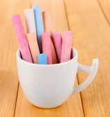 Colorful chalk in cup on table — Stok fotoğraf