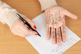 Write cheat sheet on hand on wooden table close-up — Stock Photo
