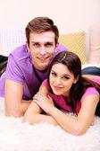 躺在家里的地毯上的年轻夫妇 — 图库照片