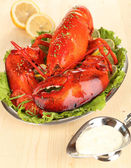 Red lobster on platter with vegetables on wooden table close-up — Stock Photo