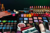 Lot of different cosmetics on green background — Stock Photo