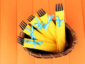 Blue plastic forks wrapped in yellow paper napkins, in wicker basket, on color wooden background — Stock Photo