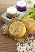 Hand-made soap and sea salt on grey bamboo mat — Stockfoto