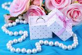 Róża i pierścionek zaręczynowy na niebieski tkaniny — Zdjęcie stockowe