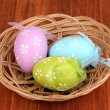 colorful easter eggs in basket on wooden background — Stock Photo #24014693