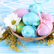 Easter eggs in basket and mimosa flowers, on blue wooden background - Stockfoto