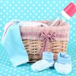 Beautiful basket of baby clothes on a blue background - Stock Photo