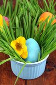 木製のテーブルには草をボウルでイースターの卵をクローズ アップ — ストック写真
