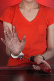 Prisoner in handcuffs behind glass in soundproof room — Stock Photo