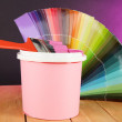 Paint pot, paintbrush and coloured swatches on wooden table on dark purple background — Stock Photo